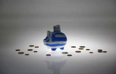 Piggybank painted in colours of Greek flag stands amongst various euro coins in this