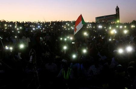 Sudanese demonstrators use their mobile phones torches as electric lamps as they attend a mass anti-government protest outside Defence Ministry in Khartoum, Sudan April 21, 2019. REUTERS/Mohamed Nureldin Abdallah