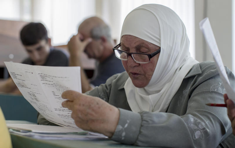 In this Monday, July 23, 2012 photo Farida Rauf Husen, an ethnic Circassian refugee from Syria reads a Russian text during a lesson in Nalchik, Russia, Monday, July 23, 2012. Some 340 ethnic Circassians from Syria have come to Russia's Caucasus region this year. Czarist troops and Cossacks expelled hundreds of thousands of Circassians in the 1860s in what some historians call a genocide and an ethnic cleansing. (AP Photo/Misha Japaridze)