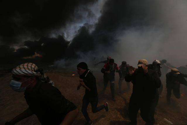 <p>Palestinian demonstrators run for cover during a protest against the U.S. Embassy's move to Jerusalem and ahead of the 70th anniversary of Nakba, at the Israel-Gaza border in the southern Gaza Strip, May 14, 2018. (Photo: Ibraheem Abu Mustafa/Reuters) </p>
