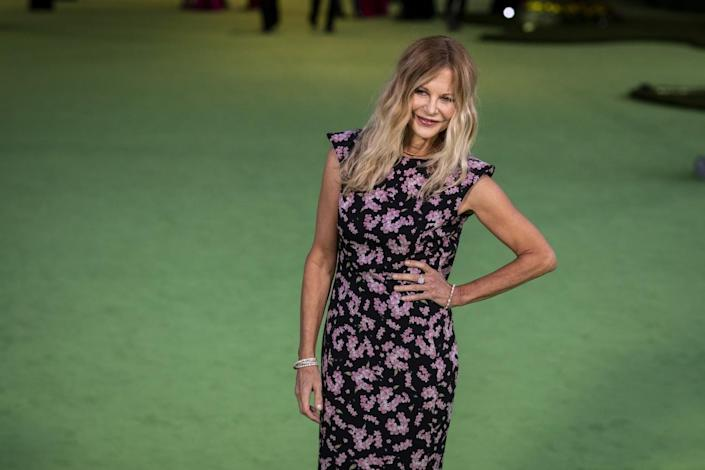 A woman in a floral dress posing on a green carpet