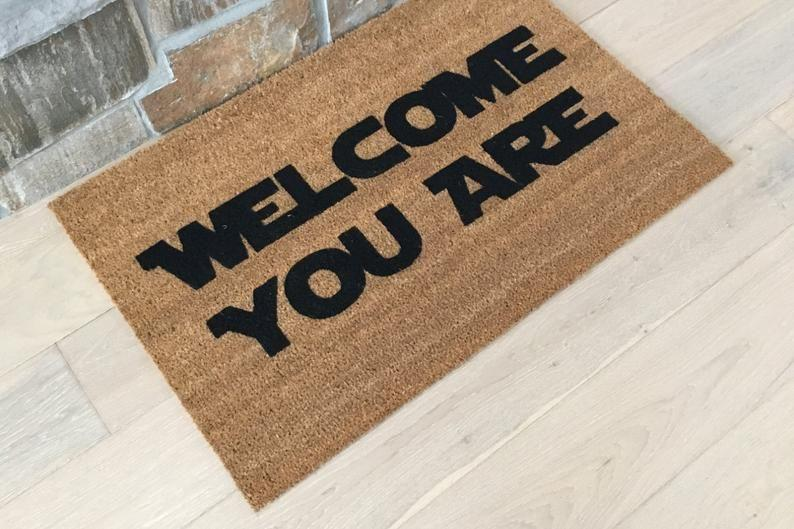 """<p><strong>GoodDayDoormats</strong></p><p>etsy.com</p><p><strong>$45.00</strong></p><p><a href=""""https://go.redirectingat.com?id=74968X1596630&url=https%3A%2F%2Fwww.etsy.com%2Flisting%2F503285391%2Fstar-wars-doormat-yoda-doormats-custom&sref=https%3A%2F%2Fwww.delish.com%2Fkitchen-tools%2Fcookware-reviews%2Fg29568867%2Fstar-wars-gifts%2F"""" rel=""""nofollow noopener"""" target=""""_blank"""" data-ylk=""""slk:BUY NOW"""" class=""""link rapid-noclick-resp"""">BUY NOW</a></p><p>No, you didn't read that wrong—this mat is written in Yoda-speak.</p>"""