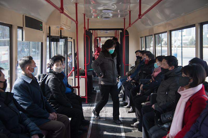 Commuters wearing face masks ride a tramcar in Pyongyang on February 26, 2020. - The novel coronavirus has killed over 2,700 people and infected more than 80,000 in 34 countries, although the vast majority of cases remain in China, according to the World Health Organization (WHO). (Photo by KIM Won Jin / AFP) (Photo by KIM WON JIN/AFP via Getty Images)