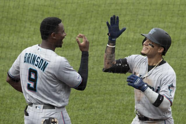 Miami Marlins' Isan Diaz, right, celebrates after hitting a home run in his major league debut with Lewis Brinson (9) during the sixth inning of a baseball game against the New York Mets, Monday, Aug. 5, 2019, in New York. (AP Photo/Mary Altaffer)