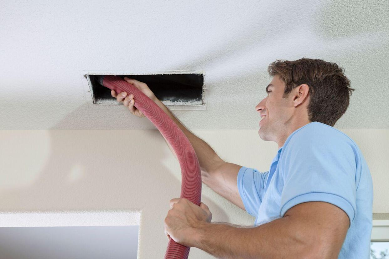 man cleaning duct and vent