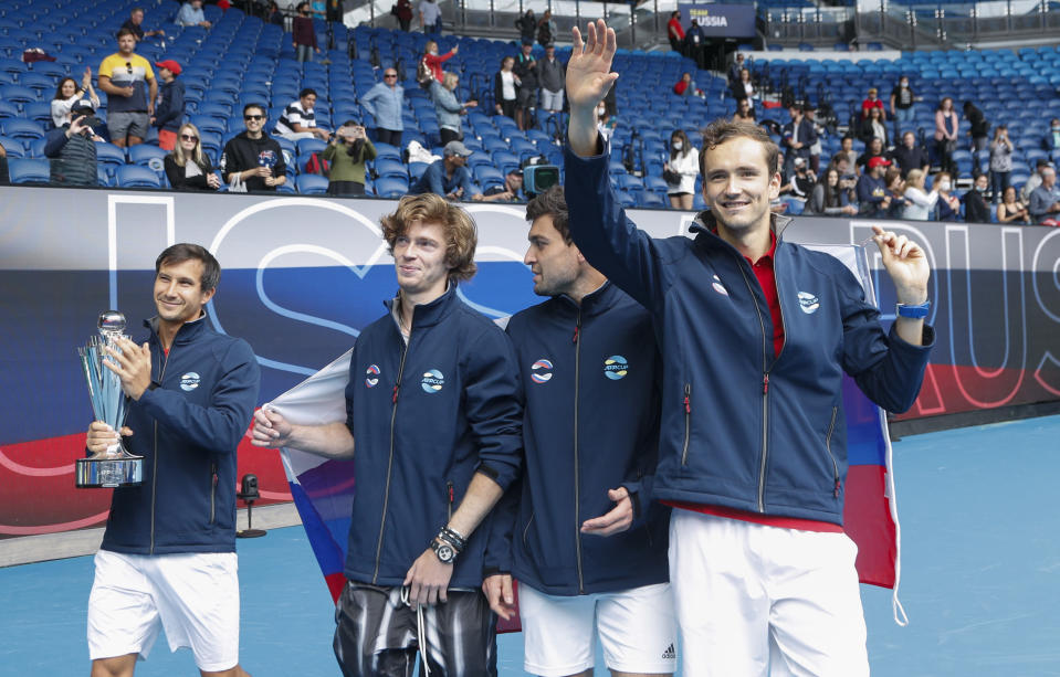 Russia's ATP Cup winners Daniil Medvedev,right, Andrey Rublev second left, Aslan Karatsev and Evgeny Donsky, left, wave to the crowd after defeating Italy in the final in Melbourne, Australia, Sunday, Feb. 7, 2021.(AP Photo/Hamish Blair)