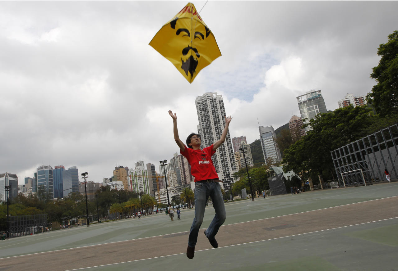 A pro-democracy protester releases a kite depicting detained Chinese artist Ai Weiwei during a protest to demand the release of the outspoken government critic, in Hong Kong, Monday, May 2, 2011.