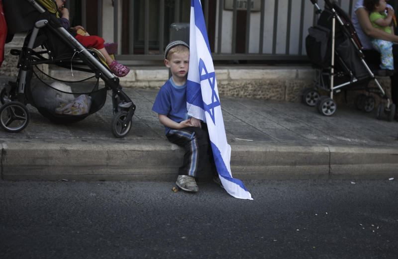 An Israeli boy sits with his national flag before an agricultural parade celebrating Jerusalem, in downtown Jerusalem, Monday, May 30, 2011. (AP Photo/Tara Todras-Whitehill)