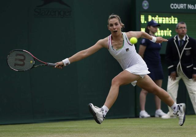 Marina Erakovic of New Zealand returns a shot against Urszula Radwanska of Poland during a first round women's singles match at the All England Lawn Tennis Championships at Wimbledon, England, Tuesday, June 26, 2012. (AP Photo/Alastair Grant)