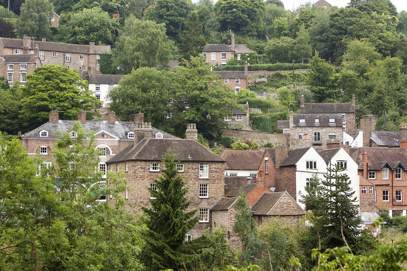 Colour photograph of trees and houses in Ironbridge a settlement on the River Severn, at the heart of the Ironbridge Gorge, in Shropshire, England.