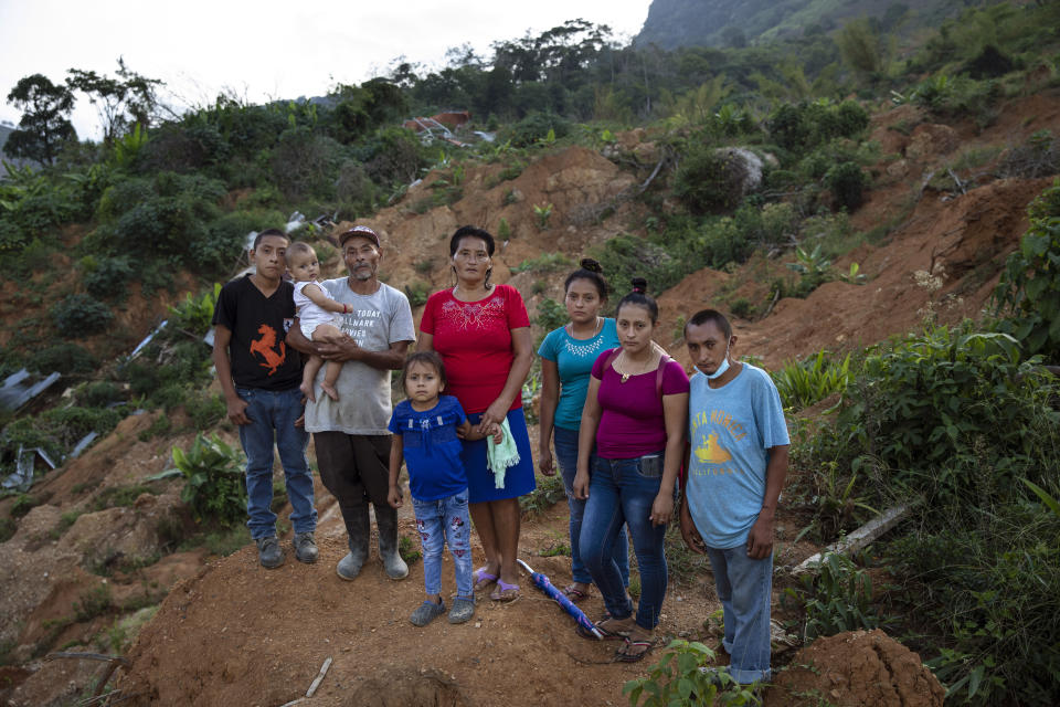 """From left, Melvin Alonso, 14; Guillermo Alonso, 54; Elvin Alonso, 6 months; Maria Orellana, 52; Genesis Alonso, 6; Yenny Alonso, 16; Areli Alonso, 22, and Orlin Alonso, 25, stand for a photo at the site where their home was destroyed by a landslide triggered by hurricanes Eta and Iota in the village of La Reina, Honduras, Thursday, June 24, 2021. """"We feel sad because we are homeless, but the important thing is that the whole family is alive,"""" says Guillermo. (AP Photo/Rodrigo Abd)"""