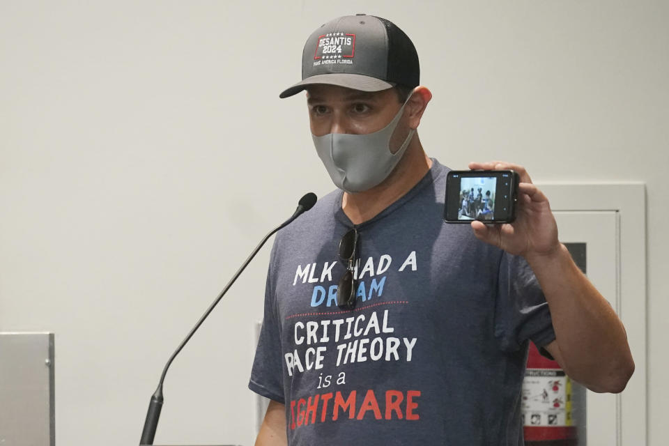 Elon Gerberg holds up a picture of his two young children singing and dancing at a private daycare, during the Broward School Board's emergency meeting, Wednesday, July 28, 2021, in Fort Lauderdale, Fla. The board listened to parents' concerns and will make a decision regarding the use of masks for K-12 students in the upcoming school year. (AP Photo/Marta Lavandier)