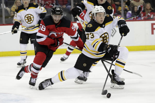 Boston Bruins defenseman Charlie McAvoy (73) stops a shot as New Jersey Devils center Kevin Rooney (58) watches during the second period of an NHL hockey game Thursday, March 21, 2019, in Newark, N.J. (AP Photo/Julio Cortez)