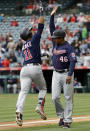 Minnesota Twins' Jorge Polanco (11) celebrates his two-run home run with third base coach Tony Diaz (46) during the second inning of a baseball game against the Los Angeles Angels Thursday, May 23, 2019, in Anaheim, Calif. (AP Photo/Marcio Jose Sanchez)