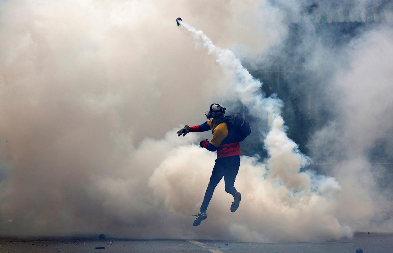 <p>An opposition supporter throws tear gas at riot police during a rally against President Nicolas Maduro in Caracas, Venezuela, May 8, 2017. (Carlos Garcia Rawlins/Reuters) </p>