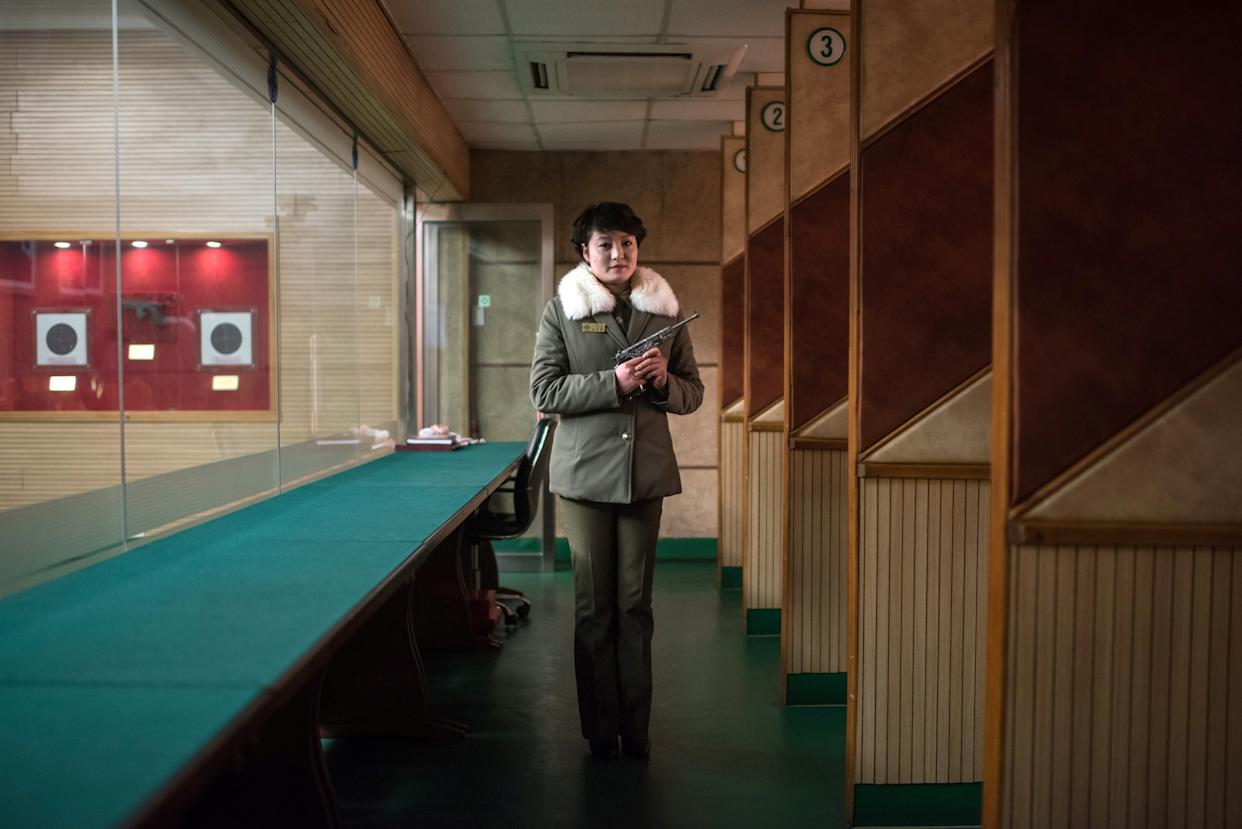 Shooting instructor Kim Su-Ryon poses for a portrait at the Meari Shooting Range in Pyongyang. Kim is holding a Paektusan target pistol, gifted by late North Korean leader Kim Il-Sung. Visitors to the range can pay $10 to shoot 10 rounds.
