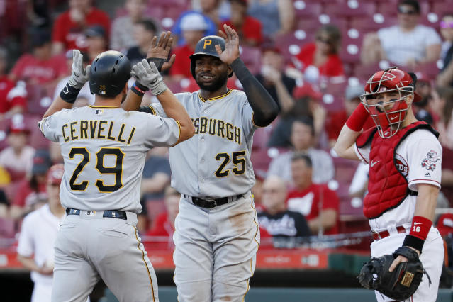 Pittsburgh Pirates' Francisco Cervelli (29) celebrates with Gregory Polanco (25) alongside Cincinnati Reds catcher Tucker Barnhart, right, after hitting a two-run home run off starting pitcher Homer Bailey during the first inning of a baseball game, Wednesday, May 23, 2018, in Cincinnati. (AP Photo/John Minchillo)
