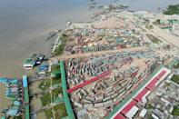 This aerial photograph taken on July 15, 2021 in Sreenagar, Bangladesh, shows vehicles waiting to get transported on ferries after the government eased a lockdown imposed against Covid-19 ahead of the Muslim festival of Eid al-Adha