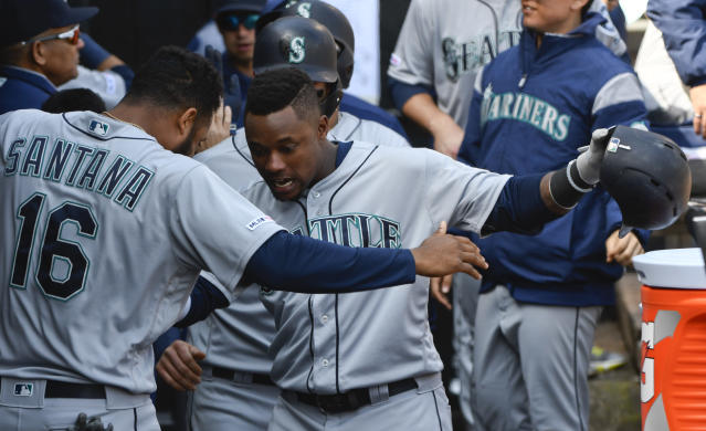 Seattle Mariners' Tim Beckham, right, celebrates in the dugout with Domingo Santana (16) after hitting a three-run home run against the Chicago White Sox during the fifth inning of a baseball game in Chicago, Saturday, April 6, 2019. (AP Photo/Matt Marton)