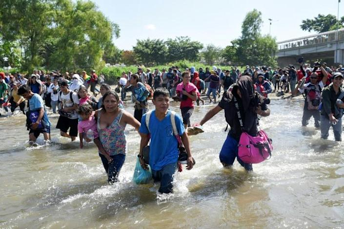 Central American migrants -- mostly Hondurans travelling in a caravan to the US -- cross the Suichate River between Guatemala and Mexico, where Mexican forces fired tear gas trying to force them back (AFP Photo/Johan ORDONEZ, Johan ORDONEZ)
