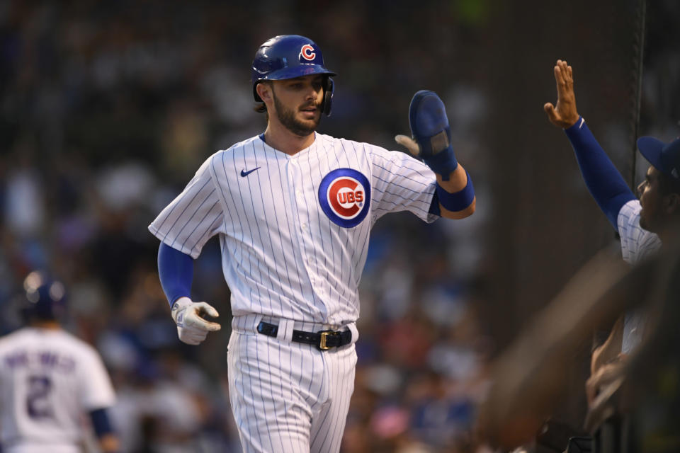 Chicago Cubs' Kris Bryant, front left, celebrates at the dugout after scoring on a David Bote single during the third inning of a baseball game against the Cincinnati Reds, Monday, July 26, 2021, in Chicago. (AP Photo/Paul Beaty)