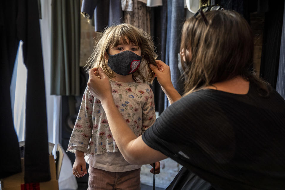"""BERLIN, GERMANY - APRIL 22: A boutique shopkeeper Xana Yva Zepplin puts on a protective mask to her daughter as she prepares to open her """"Rau Berlin"""" store for the first time since March during the novel coronavirus (COVID-19) pandemic on April 22, 2020 in Berlin, Germany. Small to midsize-shops are opening across Germany this week as state authorities follow a recommendation by the federal government to ease restrictions imposed in March meant to slow the spread of the coronavirus. Some schools are also planning to reopen soon, as are museums and hair salons in coming weeks. (Photo by Maja Hitij/Getty Images)"""
