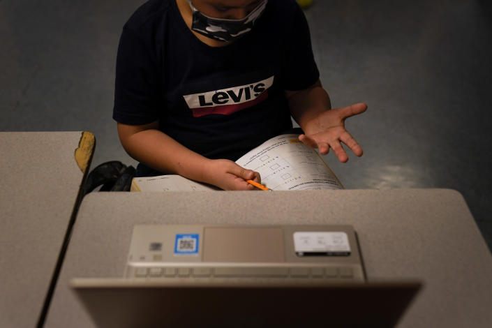 A Los Angeles Unified School District student uses his fingers to solve a math problem while taking an online class at Boys & Girls Club of Hollywood in Los Angeles. (AP Photo/Jae C. Hong)