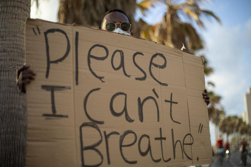 A protester holds a sign during a protest to decry the killing of George Floyd in front of the American embassy in Tel Aviv, Israel, Tuesday, June 2, 2020.(AP Photo/Ariel Schalit)
