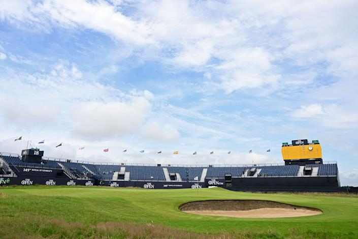 Flags flutter in the breeze above the empty stands around the 18th green during practice for The 149th British Open Golf Championship at Royal St George's, Sandwich in south-east England on July 12, 2021. - RESTRICTED TO EDITORIAL USE (Photo by Paul ELLIS / AFP) / RESTRICTED TO EDITORIAL USE (Photo by PAUL ELLIS/AFP via Getty Images)