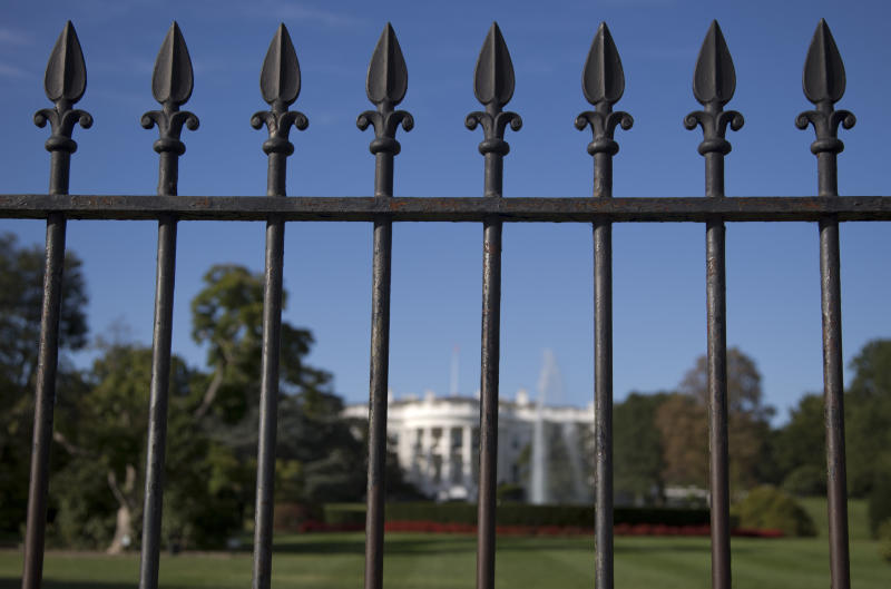 In this photo taken sept. 22, 2014, the iron perimeter fence lines the South Lawn of the White House in Washington. Two Secret Service officers who were on duty the night a man jumped the White House fence and spent more than 15 minutes roaming the grounds have been told the agency intends to fire them.  (AP Photo/Carolyn Kaster)