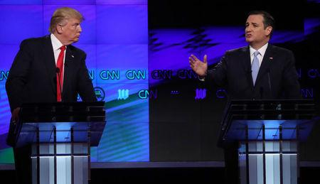 Republican U.S. presidential candidate Trump listens to rival Cruz during the Republican candidates debate in Miami
