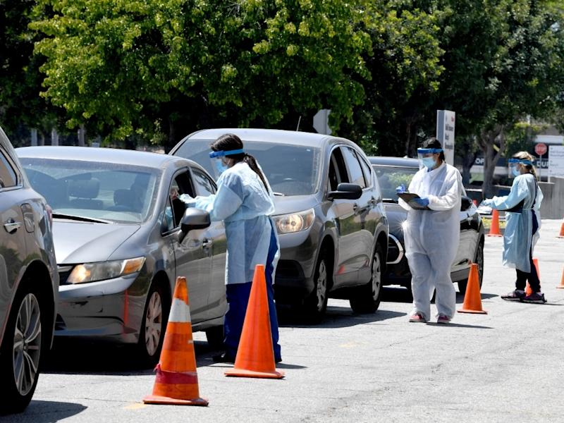 Workers wearing personal protective equipment (PPE) perform drive-up COVID-19 testing administered from a car at Mend Urgent Care testing site for the novel coronavirus at the Westfield Fashion Square on May 13, 2020 in the Sherman Oaks neighborhood