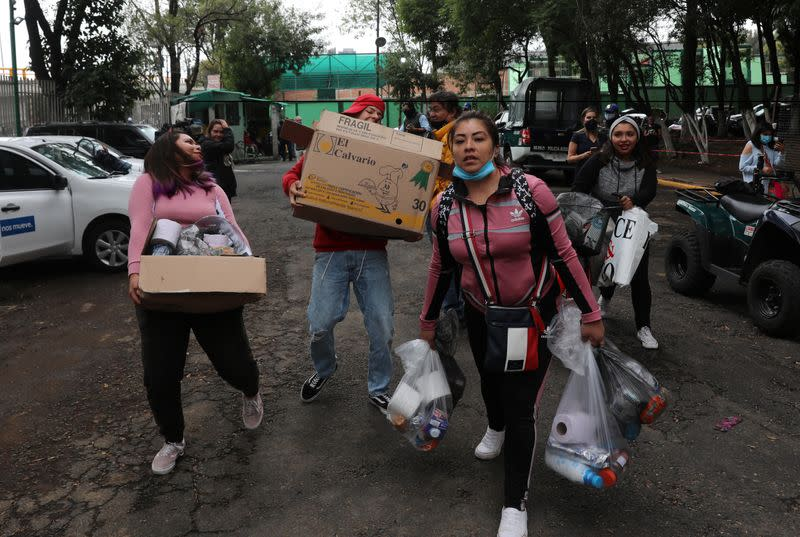 People arrive with donations of food and items for residents of an apartment building damaged by an earthquake that struck southern Mexico on Tuesday, in Mexico City