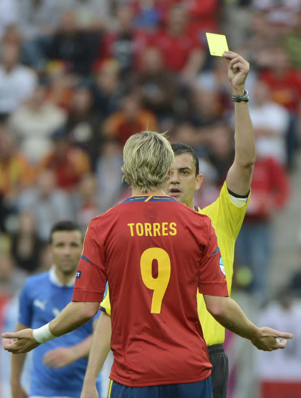 Spanish forward Fernando Torres is given a yellow card by Hungarian referee Viktor Kassai during the Euro 2012 championships football match Spain vs Italy on June 10, 2012 at the Gdansk Arena. AFP PHOTO / PIERRE-PHILIPPE MARCOUPIERRE-PHILIPPE MARCOU/AFP/GettyImages