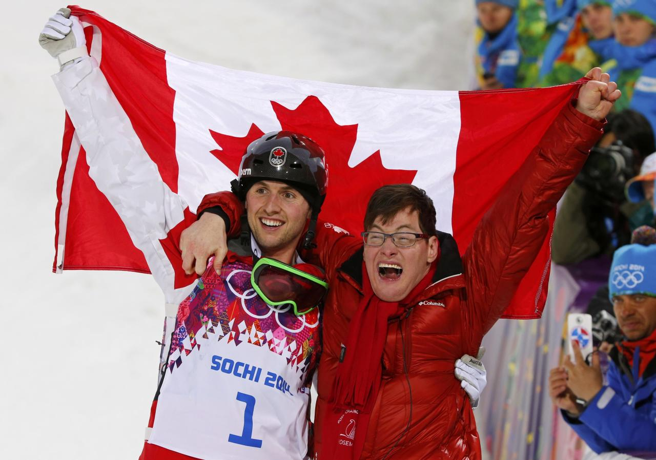 Winner Canada's Alex Bilodeau (L) and his brother Frederic celebrate with the Canadian flag after the men's freestyle skiing moguls competition at the 2014 Sochi Winter Olympic Games in Rosa Khutor February 10, 2014. REUTERS/Mike Blake (RUSSIA - Tags: SPORT SKIING OLYMPICS TPX IMAGES OF THE DAY)