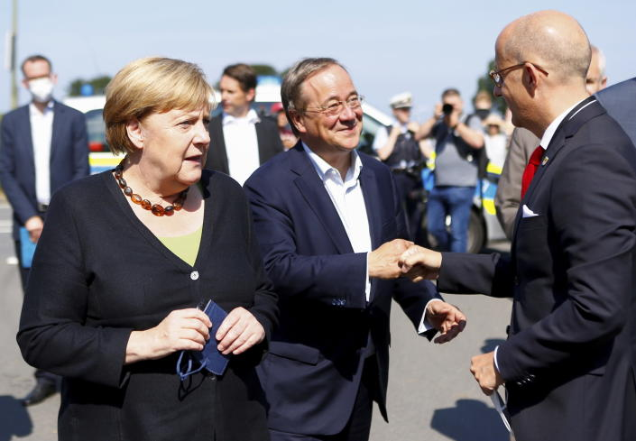 German Chancellor Angela Merkel and North Rhine-Westphalia's State Premier, chairman of the Christian Democratic Union party and candidate for Chancellery Armin Laschet, center, visit the fire station in Schalksmuehle, Germany, Sunday Sept. 5, 2021. (Thilo Schmuelgen/Pool via AP)