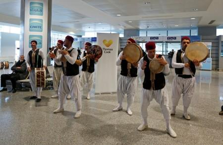 FILE PHOTO: Members of a traditional music group perform as tourists traveling with the Thomas Cook travel agency arrive at the Enfidha Airport in Enfidha
