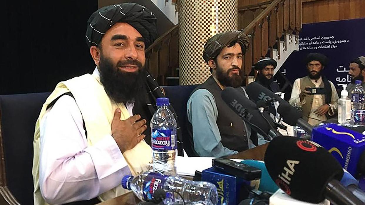 Taliban spokesman Zabihullah Mujahid, left, arrives to hold the first press conference in Kabul on Tuesday after the Taliban's swift takeover of Afghanistan.