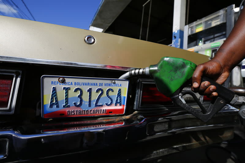 A worker fills up a car with fuel at a gas station in Caracas