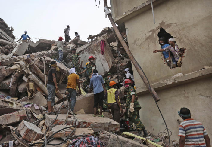 In this April 26, 2013 file photo, Bangladeshi rescue workers search for victims amid the rubble of a collapsed building in Savar, near Dhaka, Bangladesh. After more than 1,100 people died when a garment factory complex collapsed in Dhaka, Bangladesh authorities imposed more stringent safety rules. But corruption and lax enforcement have resulted in many more deaths linked to safety lapses since the 2013 Rana Plaza disaster, including a fire Thursday in an illegally-constructed high-rise office building that killed at least 25 people and left dozens more injured. (AP Photo/Kevin Frayer, File)