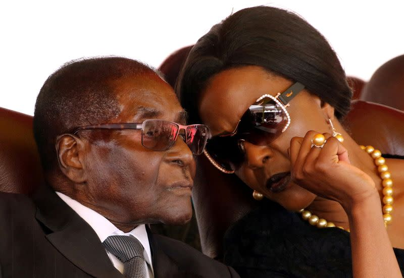 FILE PHOTO: Mugabe and his wife Grace attend the burial of two independence luminaries in Harare