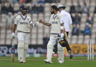 India's captain Virat Kohli, right, fist bumps with batting partner Ajinkya Rahane as they walk off the field after bad light stopped play during the second day of the World Test Championship final cricket match between New Zealand and India, at the Rose Bowl in Southampton, England, Saturday, June 19, 2021. (AP Photo/Ian Walton)