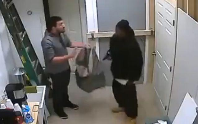 The armed robber gives the man a grey bag to put phones, cash and other products in. Source: LiveLeak.