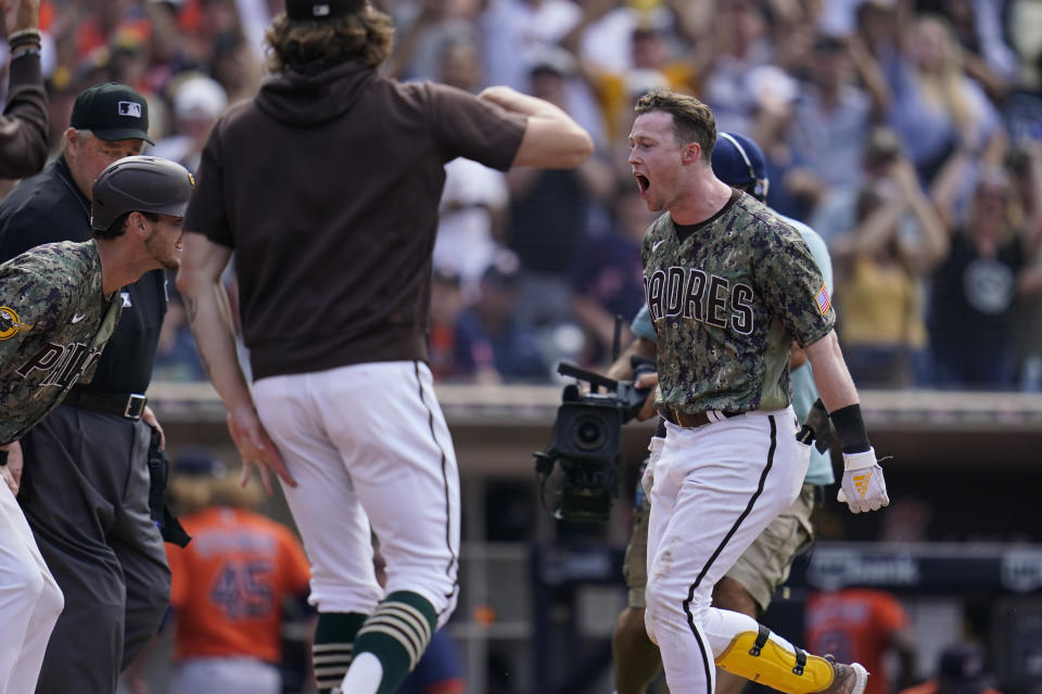 San Diego Padres' Jake Cronenworth, right, reacts with teammates after hitting a walk-off home run during the ninth inning of a baseball game against the Houston Astros, Sunday, Sept. 5, 2021, in San Diego. The Padres won, 4-3. (AP Photo/Gregory Bull)