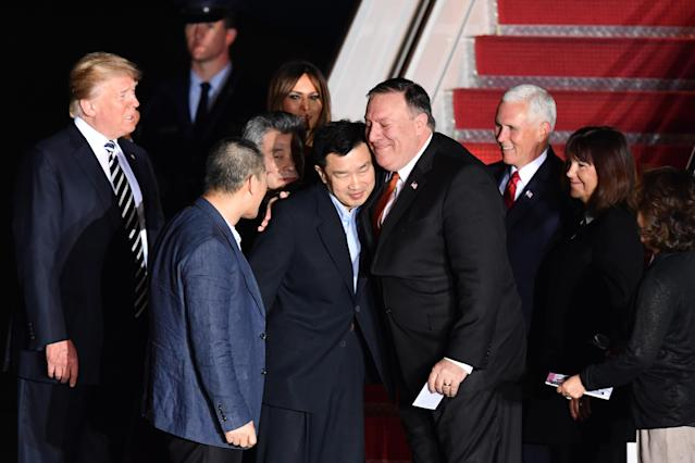 <p>President Donald Trump (L) looks on as U.S. detainees Tony Kim (center L) receives a hug from Secretary of State Mike Pompeo upon their return after they were freed by North Korea, at Joint Base Andrews in Maryland on May 10, 2018. (Photo: Nicholas Kamm/AFP/Getty Images) </p>