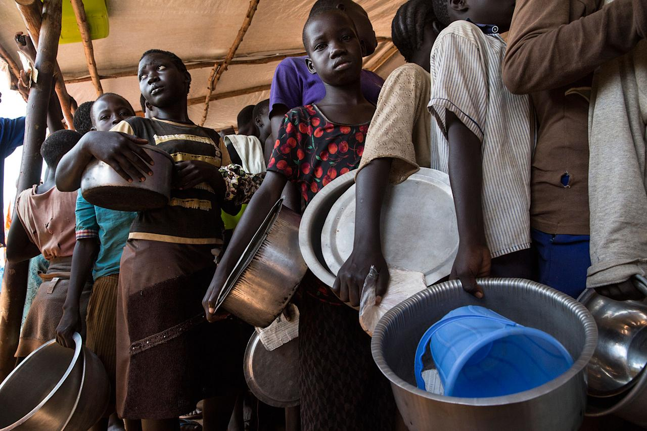 <p>At the Nyumanzi transit center in Adjumani District in Gulu, Uganda, September 2016, refugees line up for hours to receive a hot meal from World Food Program (WFP) . (Photograph by Paula Bronstein) </p>