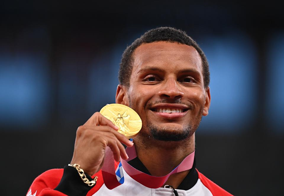 Andre De Grasse of Canada poses as he celebrates on the podium after winning gold in the men's 200m event in the 2020 Tokyo Olympics.