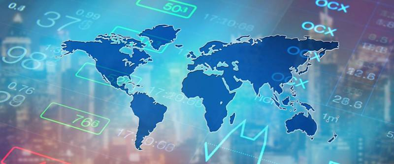 digital world map over a photo of the stock market