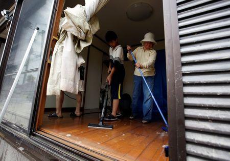 Family members of 79-year-old local resident Isao Akutagawa (not pictured), try to remove mud and debris from their house in a flood affected area in Mabi town in Kurashiki, Okayama Prefecture, Japan, July 12, 2018.  REUTERS/Issei Kato