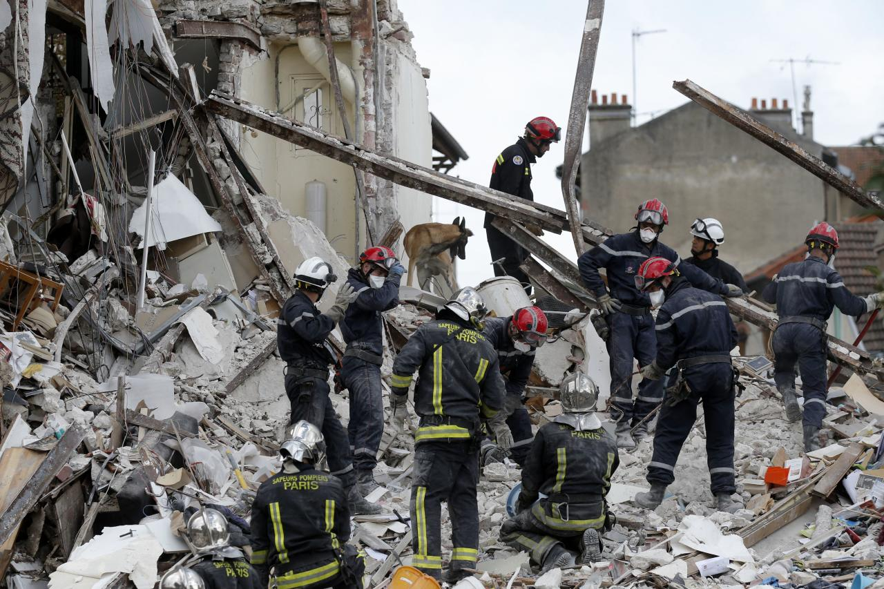 French firefighters search the rubble of a collapsed building in Rosny-Sous-Bois, near Paris August 31, 2014. A four-story building was rocked by an explosion and collapsed, killing a child, in a northeastern suburb of Paris on Sunday morning, French authorities said. Ten people, including four seriously wounded, were evacuated from the rubble of the building, and a child was killed, fire department spokesman Gabriel Plus told iTele. REUTERS/Christian Hartmann (FRANCE - Tags: DISASTER SOCIETY)